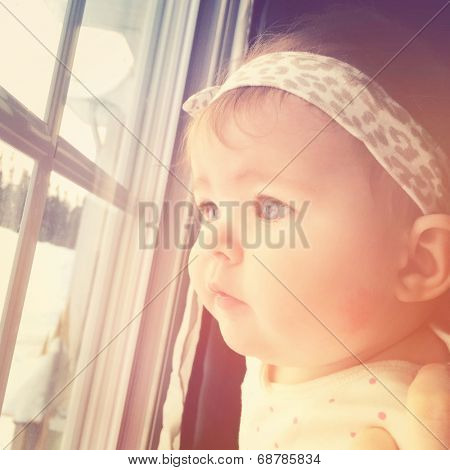 Little baby girl looking out window - With Instagram effect
