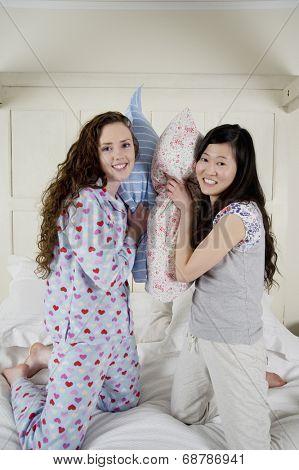 Happy female friends having pillow fight