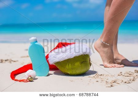 Suncream, Santa Hat on coconut and tanned female legs at white beach