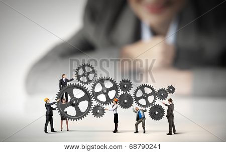 Businesswoman looking at team of businesspeople in miniature