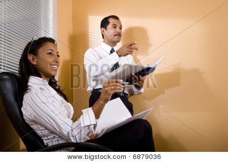 Multi-ethnic office workers in boardroom watching presentation