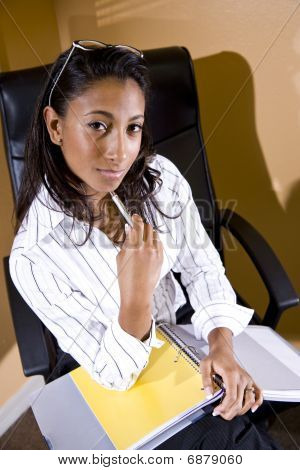 Young office worker sitting with notebook ready to take notes