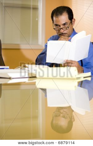 Serious middle-aged Hispanic businessman working in boardroom