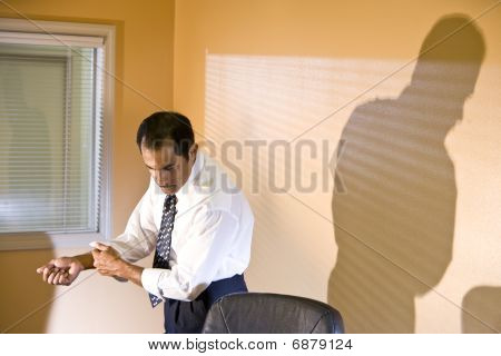 Middle-aged Hispanic businessman rolling up sleeves