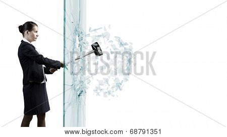 Young determined businesswoman breaking glass with hammer