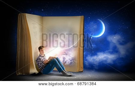 Teenager boy wearing jeans and shirt and reading book