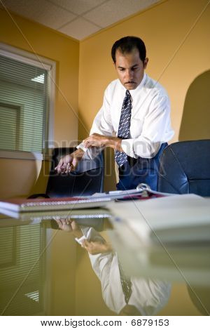 Middle-aged Hispanic businessman working in office rolling up sleeves