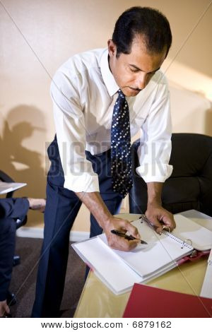 Middle-aged Hispanic businessman working in office writing notes