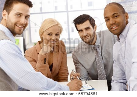 Closeup photo of happy young businessteam working together, smiling, looking at camera.