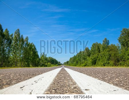 Asphalt road with center lines marking close-up