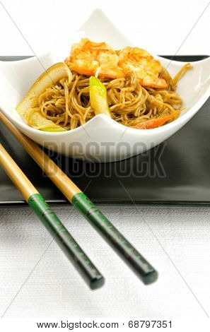 Delicious Chinese noodles topped with shrimps served in a stylish contemporary white porcelain bowl on a square black plate with chopsticks for healthy seafood cuisine, studio shot on white