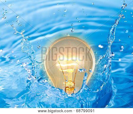 Glowing yellow light bulb of idea in water