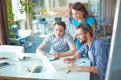image of gathering  - Group of three successful business partners in casual using laptop at meeting in office - JPG