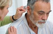 stock photo of ear  - Doctor inserting hearing aid in senior - JPG