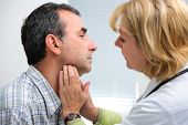 stock photo of throat  - female doctor touching the throat of a patient in the office - JPG