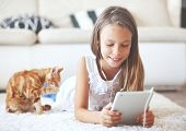 pic of pre-teen  - Pre teen girl playing on tablet pc laying down on a white carpet at home - JPG
