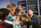 stock photo of annoying  - Annoyed male cafe worker with long line - JPG