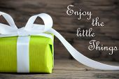 stock photo of happy day  - Green Gift with the Saying Enjoy the Little Things on wooden Background