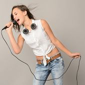picture of karaoke  - Singing teenage girl with microphone karaoke music on gray background - JPG