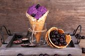 picture of cone  - Tasty ice cream with berries in waffle cone on brown wooden background - JPG