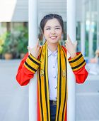 picture of polite girl  - Graduate Thai college girl in academic gown is holding poles and smiling happily for the moment - JPG