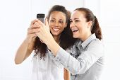 stock photo of two women taking cell phone  - Two women take pictures with your phone - JPG
