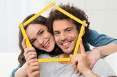 foto of love-making  - Happy Young Couple Making House Shape With Folding Ruler - JPG