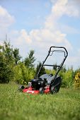 stock photo of grass-cutter  - Lawn mower on the grass during the summer day - JPG
