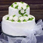 picture of icing  - Wedding cake with white frosting or icing decorated with white roses and green leaves - JPG