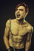 stock photo of outrageous  - Redhead chained young man screaming over dark background - JPG