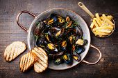 image of copper  - Mussels in copper cooking dish and french fries on dark wooden background - JPG