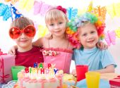stock photo of birthday party  - Three kids are happily posing during birthday party - JPG