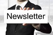 stock photo of newsletter  - businessman in black suit holding white sign newsletter - JPG