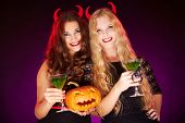 stock photo of antichrist  - Photo of smiling females holding Halloween pumpkin and cocktails with scorpions - JPG