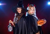 foto of antichrist  - Portrait of two females with lantern and pumpkin looking at camera in the dark - JPG