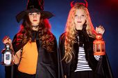 foto of antichrist  - Portrait of two Halloween girls with lanterns looking at camera - JPG