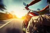 stock photo of pov  - Biker riding motorcycle  on an empty road at sunny day - JPG