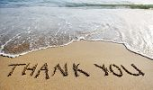 stock photo of handwriting  - thank you words written on the sand of the beach - JPG
