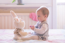 foto of cheeky  - 10 months old baby girl playing with plush rabbit - JPG
