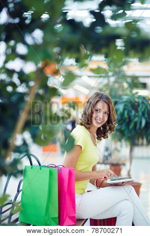 Pretty female buyer networking in the mall