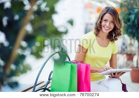 Smiling shopper using digital tablet in the mall