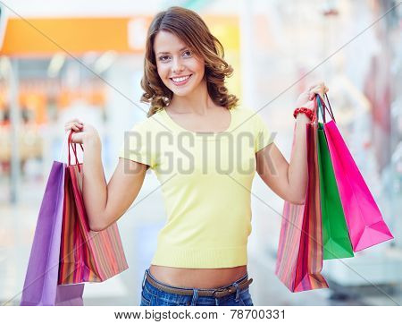 Happy shopaholic showing her shopping bags
