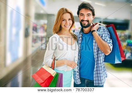 Affectionate shopaholics with paperbags looking at camera