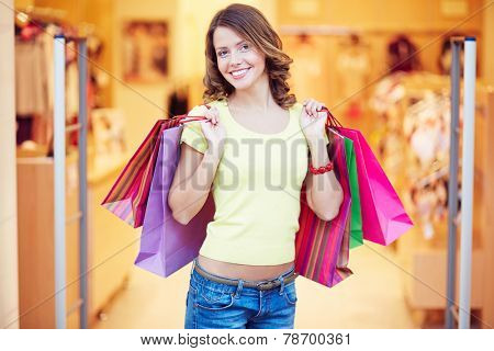 Curly-haired shopaholic with shopping bags looking at camera