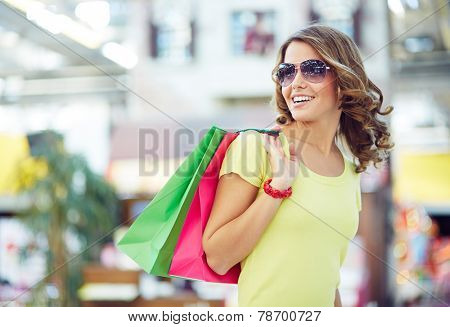Young shopaholic in sunglasses enjoying her favorite pastime