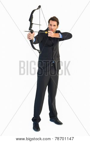 Concentrated handsome businessman practicing archery on white background