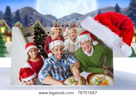 Father in santa hat carving chicken at christmas dinner against quaint town with bright moon
