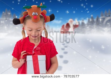 Cute little girl wearing rudolph headband against bright blue sky over clouds