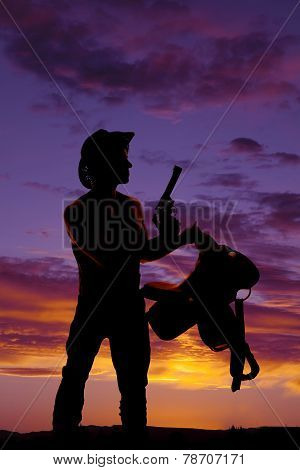 Silhouette Of A Man With A Gun And A Saddle