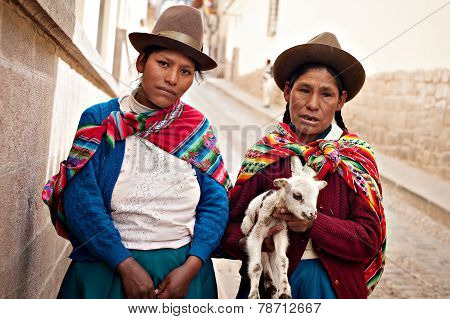 Peruvian Women In Authentic Dress With A Goat In Cusco, Peru.